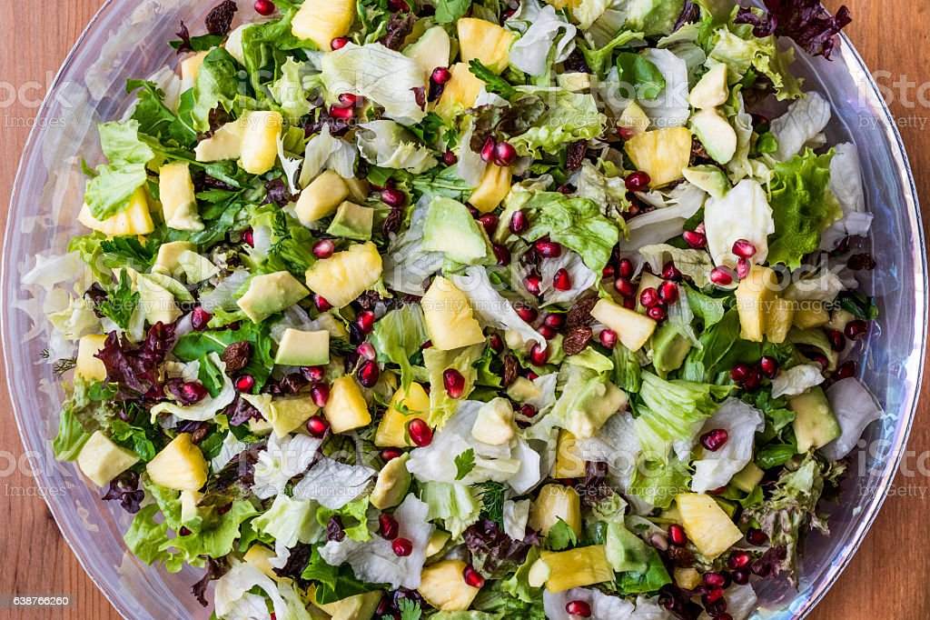 Pineapple Salad with pomegranate, raisin and greens in glass bow - foto de stock