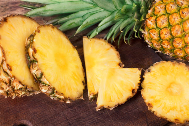 pineapple slices on wooden background - ananas zdjęcia i obrazy z banku zdjęć