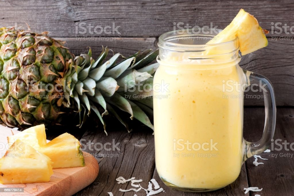Pineapple smoothie in a mason jar, scene against wood stock photo
