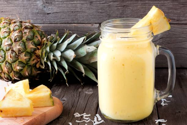 pineapple smoothie in a mason jar, scene against wood - ananas zdjęcia i obrazy z banku zdjęć