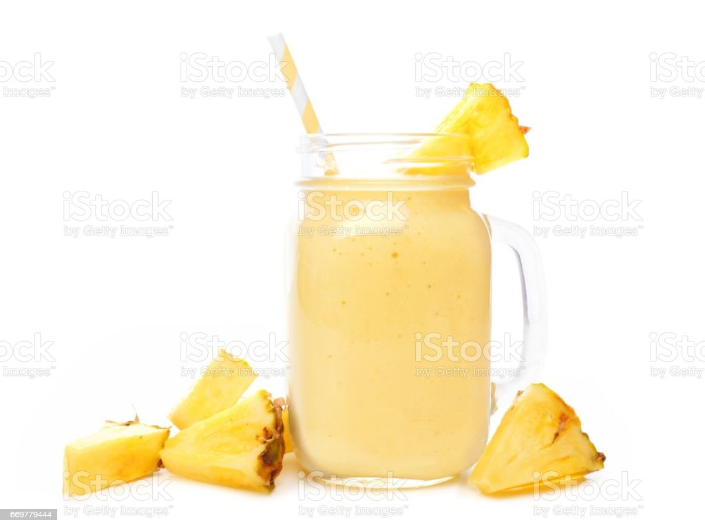 Pineapple smoothie in a mason jar with fruit slices over white - Photo