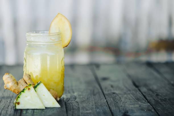 ananas-smoothie auf holz hintergrund - ingwerwasser zubereiten stock-fotos und bilder