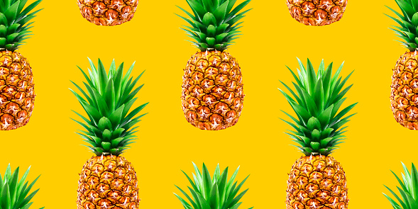 Pineapple, ananas seamless pattern. Tropical fruits on yellow background. Ripe pineapples backdrop, summer wallpaper design