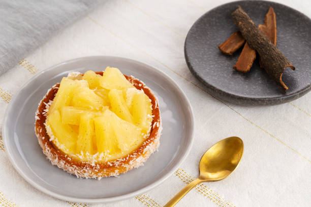 Pineapple tart or tartlet with coconut by a golden spoon and a small plate with cinnamon sticks on a white and gold table cloth. stock photo