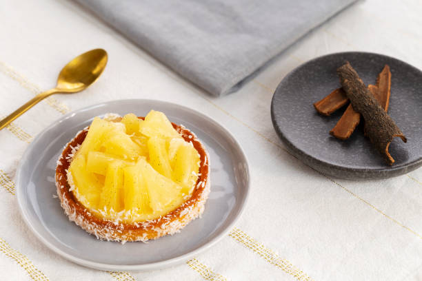 Pineapple tart or tartlet with grated coconut by a golden spoon and a small plate with cinnamon sticks on a white and gold table cloth. stock photo