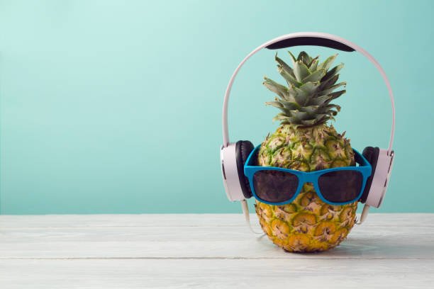 Pineapple with headphones and sunglasses on wooden table over mint background. Tropical summer vacation and beach party concept. Pineapple with headphones and sunglasses on wooden table over mint background. Tropical summer vacation and beach party concept. mp3 player stock pictures, royalty-free photos & images