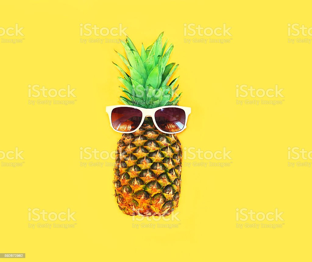 Pineapple with sunglasses on yellow background colorful ananas stock photo