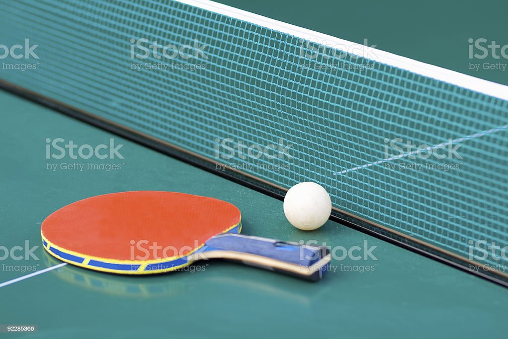 Ping pong paddle and table with net stock photo
