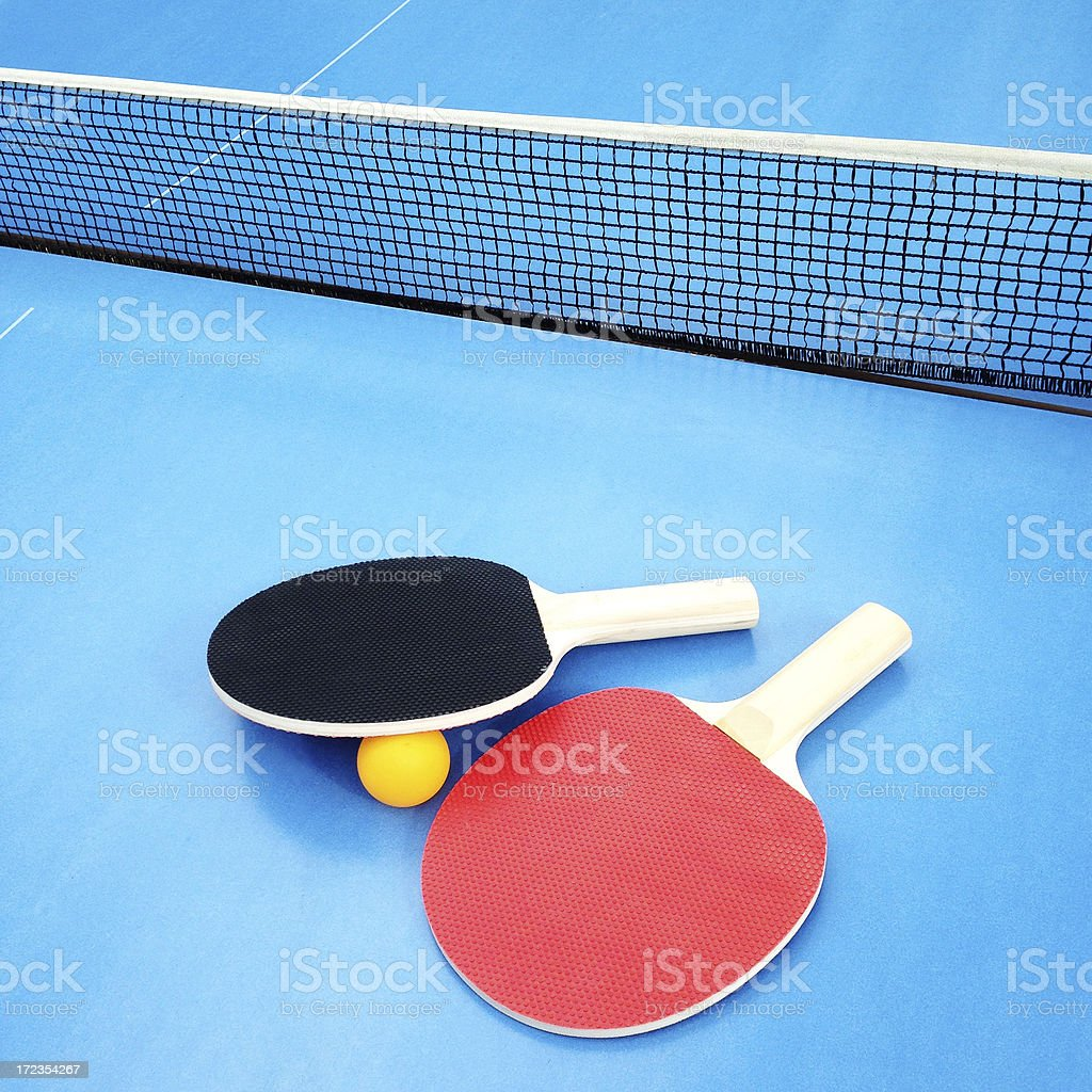 Ping pong paddles on a blue tabletennis table royalty-free stock photo