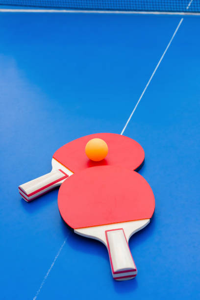 pingpong rackets and ball and net on a blue pingpong table - table tennis racket stock pictures, royalty-free photos & images