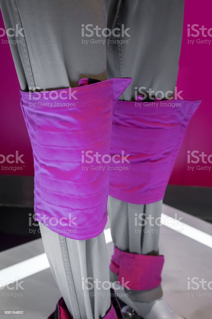 Pink adjustable training weight bags for ankle, knee, and wrist on mannequin model. Simulation elder people condition while walking. stock photo