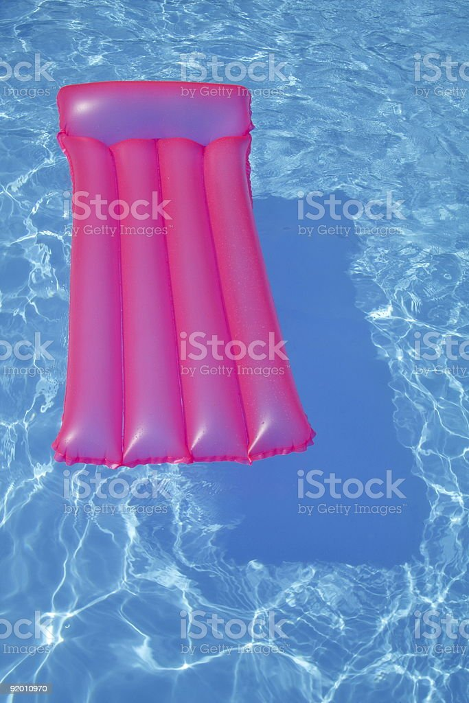 Pink air bed floating on a swimming pool royalty-free stock photo