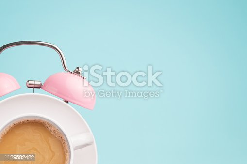 istock Pink alarm clock and coffee cup on blue background. Breakfast time concept. Minimal style 1129582422