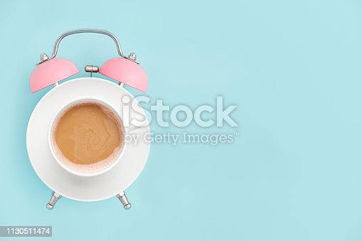 1139289535 istock photo Pink alarm clock and coffee cup on blue background. Breakfast time concept. Minimal style 1130511474