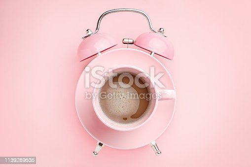 istock Pink alarm clock and coffee cup on pink background. Breakfast time concept. Minimal style 1139289535