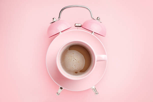 Pink alarm clock and coffee cup on pink background. Breakfast time concept. Minimal style stock photo