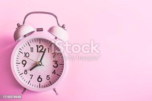1139289535 istock photo Pink alarm clock lying on pink 1216379449