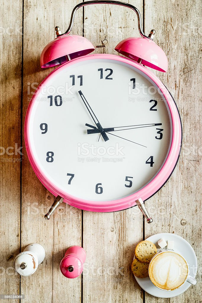 pink alarm clock on a wooden table foto royalty-free