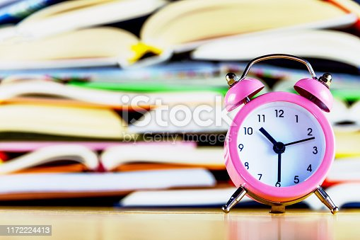 istock Pink alarm clock on background of stack of books 1172224413