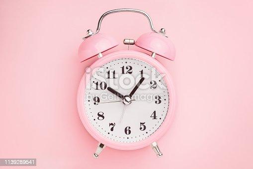 1139289535 istock photo Pink alarm clock on pink background. Minimal style 1139289541