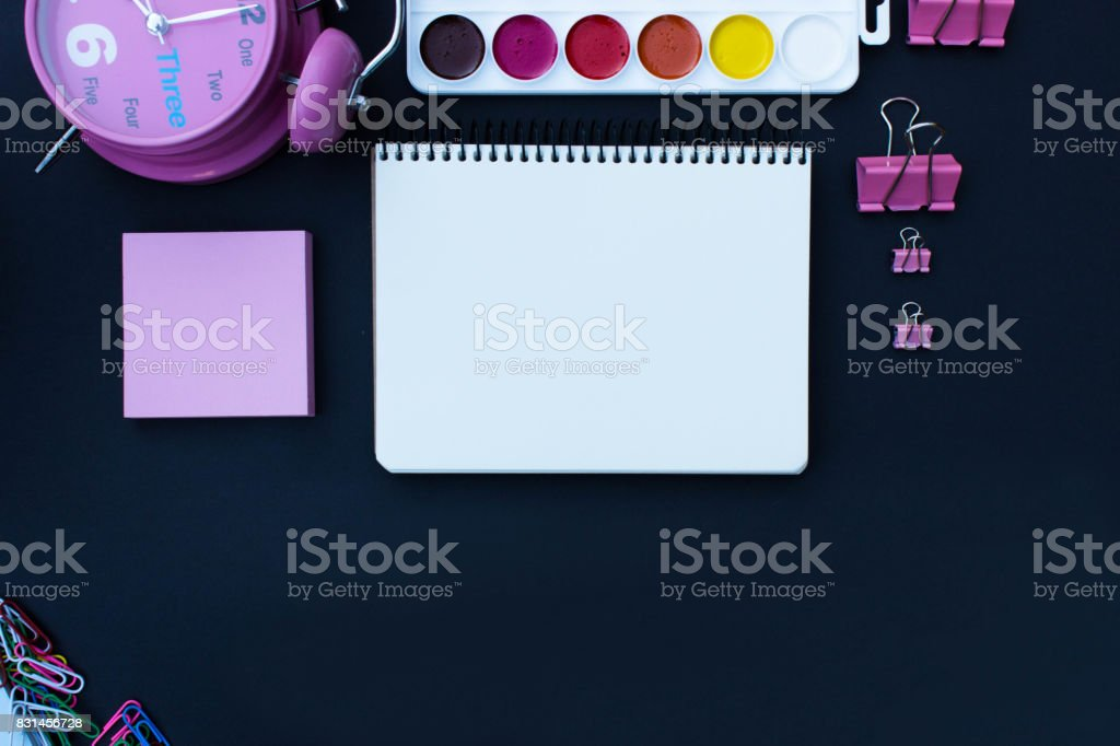 Pink alarm clock, stickers, notepad with white space, watercolor paints, binder clerical clamp, paperclip, eraser and pencil, ballpen. School supplies on blackboard or chalkboard black background. stock photo