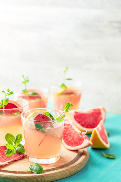 Pink alcoholic cocktail with grapefruit, ice and mint stock photo