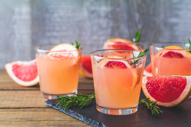 Pink alcoholic cocktail with grapefruit, ice and rosemary stock photo