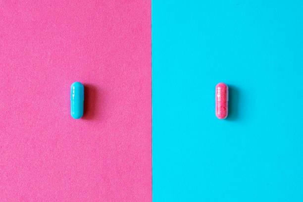 Pink and blue capsules, pills isolated on bicolor pink and blue colored background. Medication and prescription pills minimal coloured flat lay with copy space. Pharmaceutical industry minimal concept Pink and blue capsules, pills isolated on bicolor pink and blue colored background. Medication and prescription pills minimal coloured flat lay with copy space. Pharmaceutical industry minimal concept antihistamine stock pictures, royalty-free photos & images