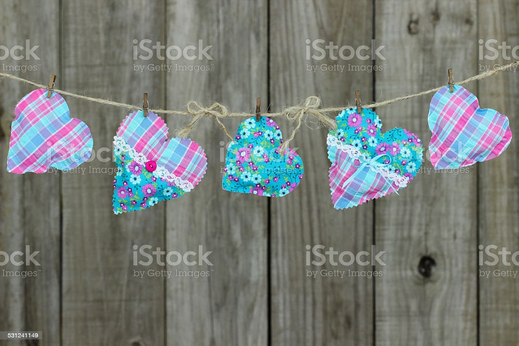 Pink and blue fabric hearts hanging on clothesline stock photo