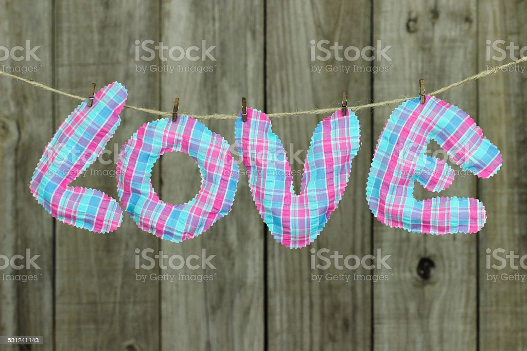 Pink and blue LOVE text hanging on clothesline stock photo