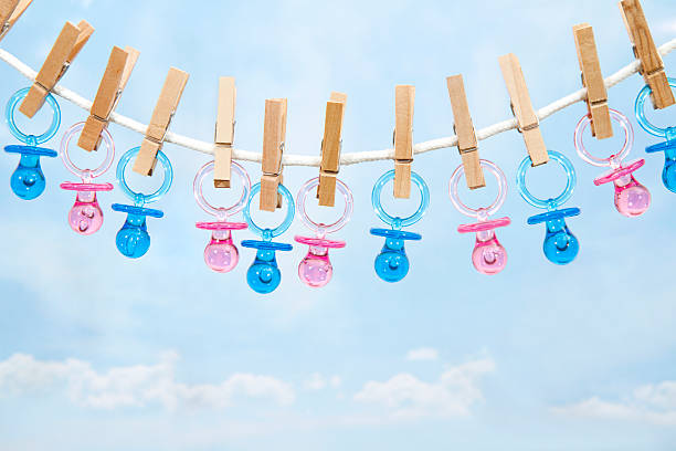 pink and blue pacifiers hanging on a clothesline - its a girl stock photos and pictures