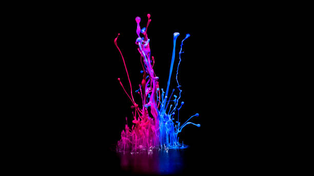 Rosa und blaue Farbe spritzt auf Lautsprecher isoliert auf schwarzem Hintergrund – Foto