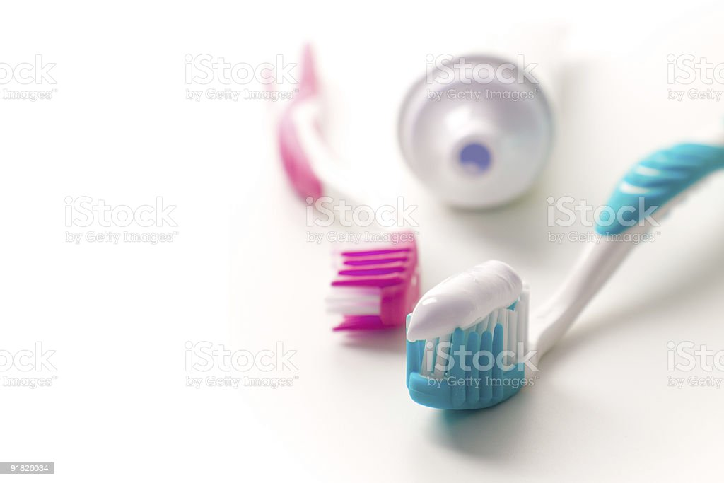 Pink and blue toothbrushes and toothpaste tube royalty-free stock photo