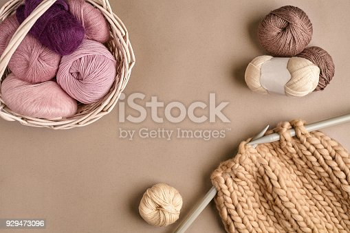 istock Pink and brown knitting wool and knitting on knitting needles on beige background. Top view. Copy space 929473096