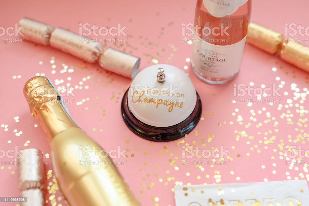 Pink and gold champagne background with bell that says Press for...