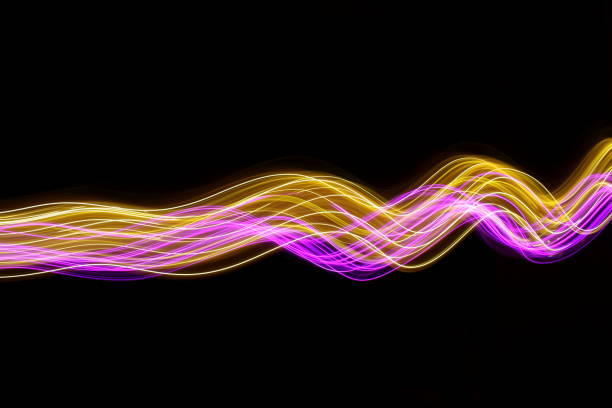 Pink and gold light painting photography, long exposure photo of fairy lights against a black background stock photo