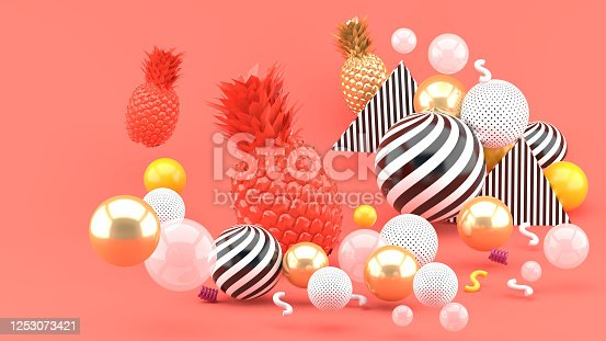 917861766 istock photo Pink and golden pineapple amidst golden balls on a pink background.-3d render. 1253073421