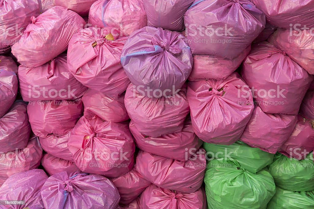 Pink and green plastic garbage bags stock photo