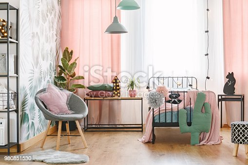 Pink pillow on grey armchair near bed in girl's bedroom interior with green cactus and lights on table