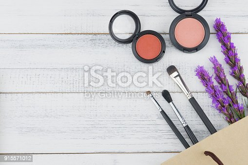 Pink and orange blush with make up brush and violet liatris flowers on white wood background with copy space