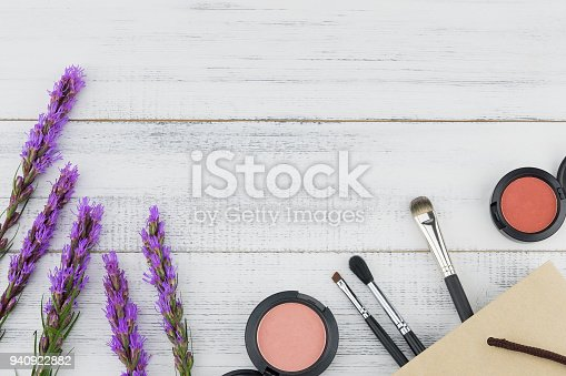 Pink and orange blush with make up brush in paper bag and violet liatris flowers on white wood background with copy space