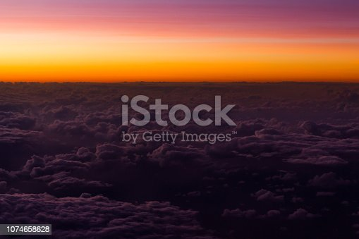 1045890176 istock photo Pink and orange sunset sky over clouds 1074658628