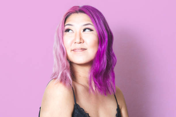Pink and Purple Hair Against Matching Pink Background – zdjęcie