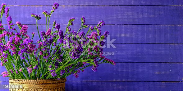 Pink and purple Statice/Limonium or sea-lavender flowers against a violet worn wood panel board background, lots of texture.