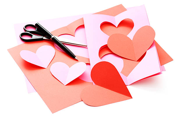 Pink and red cut-out hearts with pen and scissors on white stock photo