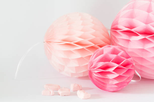 pink and salmon honeycombs with sweet candy against white background - garland decoration stock photos and pictures