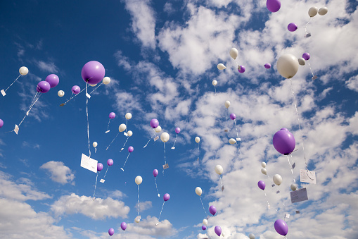 Pink and White Balloons with Postcards Flying in Sky