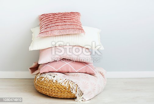 Pink and white pillows on the wall background. Close up