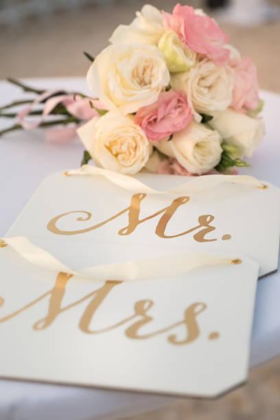 pink and white roses bridal bouquet, mr mrs wedding signs - bräutigam tisch stock-fotos und bilder