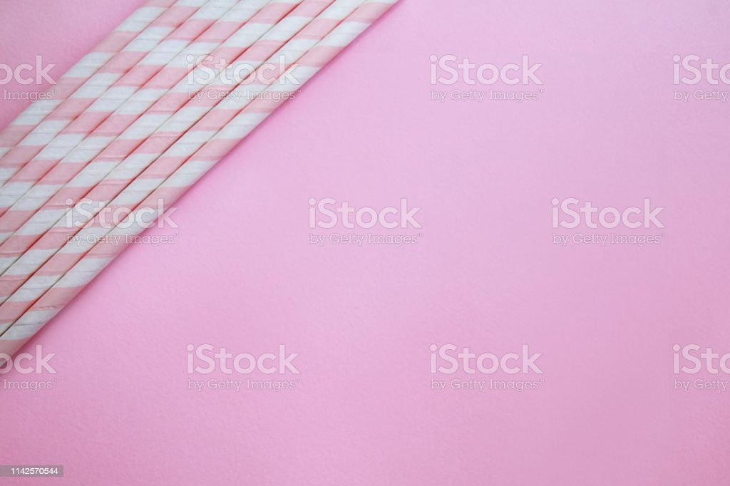 Pink and white striped paper straws on soft pink pastel background...